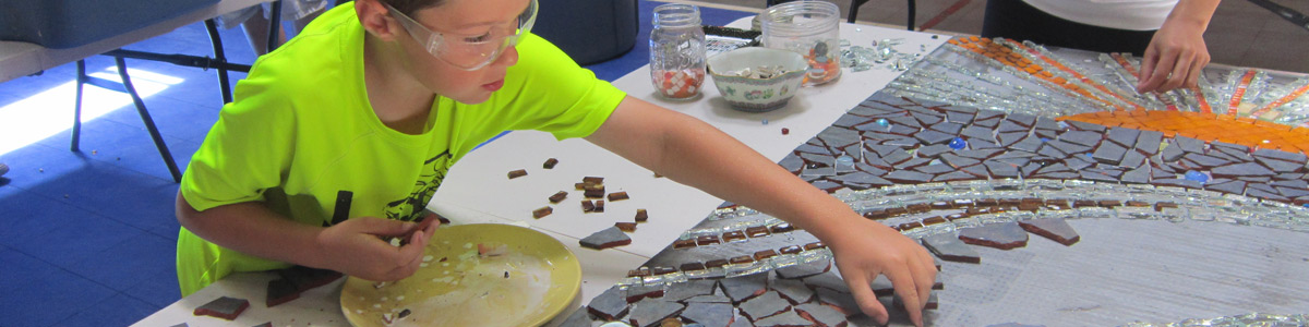 A young workshop participant works on the ARTreach mosaic mural (HCAC photo)